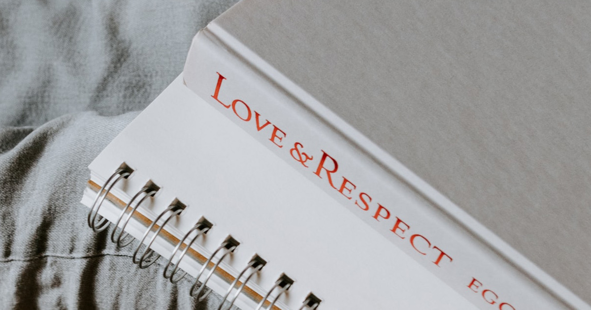 A white book with the title Love and Respect in red letters on the spine, rests on a spiral bound notebook on a woman's lap