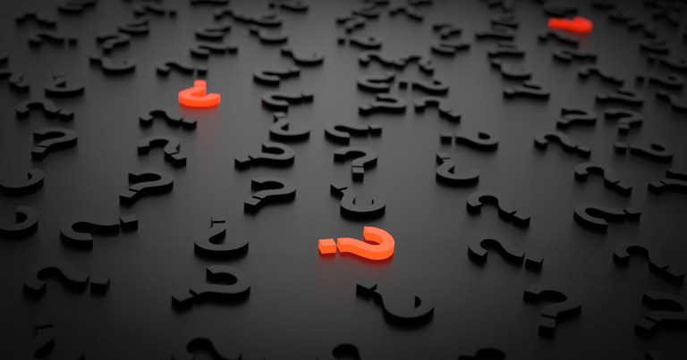 Black plastic question marks lie scattered on a black surface, three red question marks stand out in contrast.