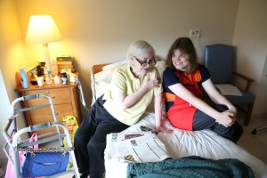 Project SEARCH intern Haley McCormick-Thompson lends an attentive ear to a resident at United Hebrew New Rochelle (photo credit POSITIVE EXPOSURE)