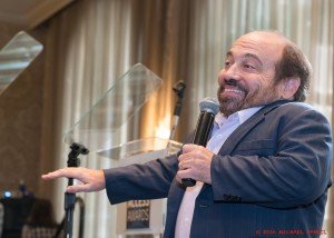 Danny Woodburn smiling and pointing
