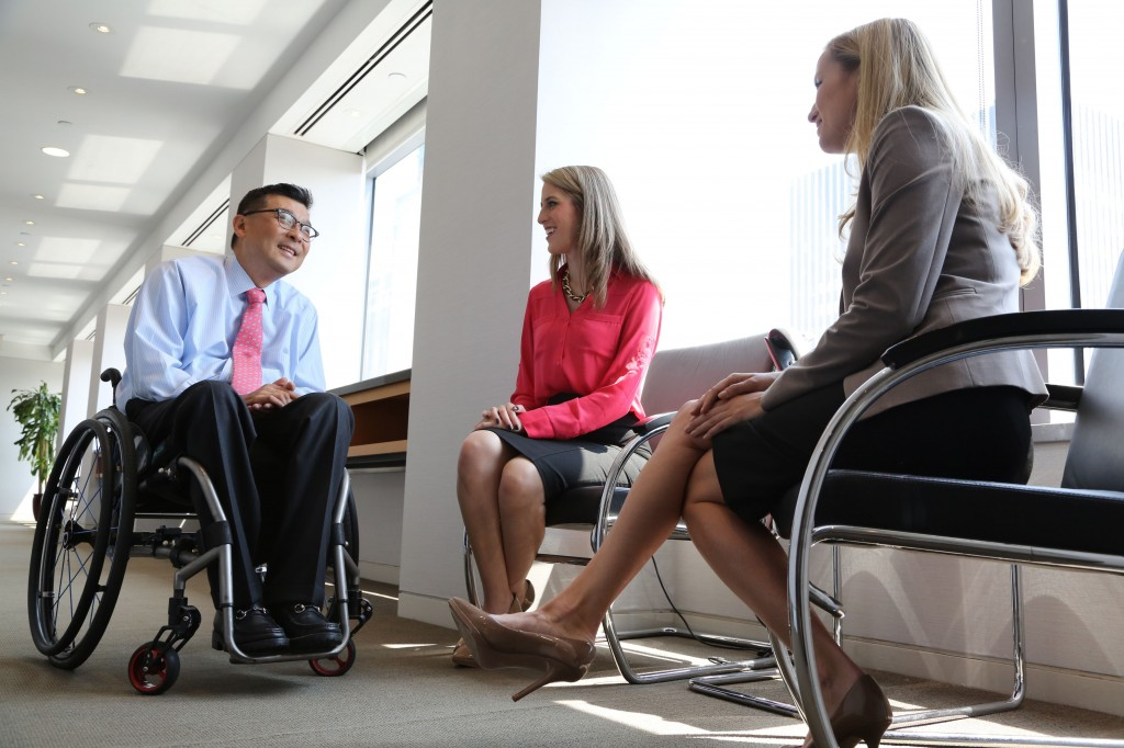 Won Shin, senior manager in transaction advisory services at EY, speaks with coworkers Alejandra Preciat and Frances Smith (photo credit POSITIVE EXPOSURE)