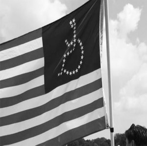 A black and white photo of an American flag with the stars in shape of a wheelchair