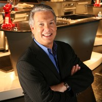 headshot of Marc Summers wearing a black suit and blue shirt with arms crossed in front of a kitchen set