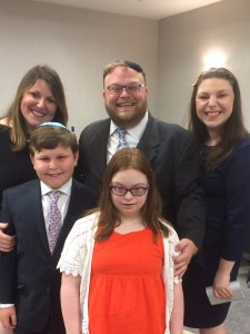 Aaron and Ahuva Orlofsky posed with their three children - teenage girl, boy and girl, all smiling for the camera