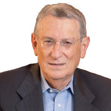 head shot of Stan Greenberg wearing a gray blazer and blue collared shirt smiling and facing the camera with a white background