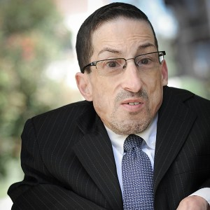 headshot of Steven James Tingus wearing a black suit and blue tie seated in his wheelchair outside color photo