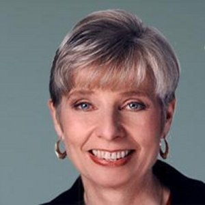 headshot of Eleanor Clift smiling and facing the camera wearing hoop earrings color photo