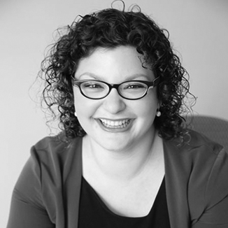 headshot of Emma Adelman smiling with curly hair grayscale photo