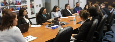 Fran Katz Watson sitting at table with Fellows around her listening to her speak