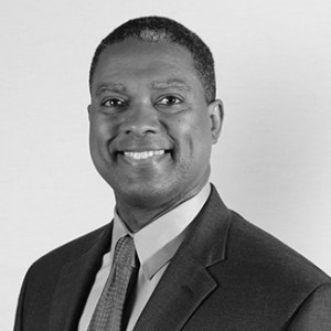 headshot of Gerard Robinson smiling and facing the camera and wearing a suit and tie grayscale photo
