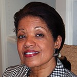 headshot of Janie L. Jeffers smiling and wearing red lipstick, earrings, and a black and white patterned jacket color photo