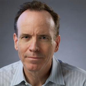 headshot of Jonathan Murray wearing a gray striped shirt and facing the camera color photo