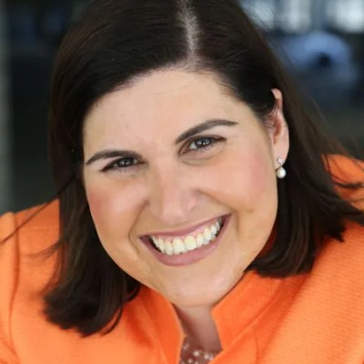 head shot of Lauren wearing an orange blazer, smiling and facing the camera