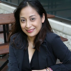 Marisela is sitting on bench smiling with a black dress and black blazer on color photo