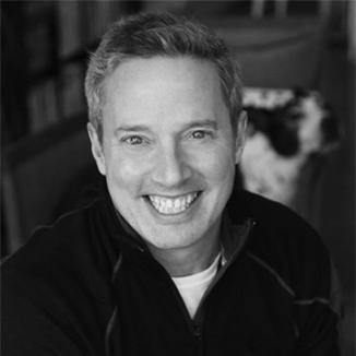 headshot of Rick Guidotti smiling and facing the camera grayscale photo