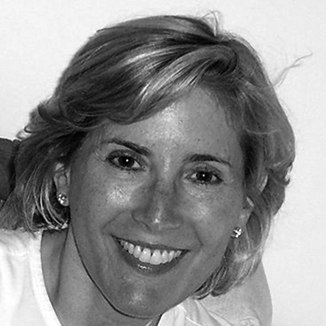 Shelley Cohen is smiling at the camera, her hair is messy and she is wearing small earrings grayscale photo