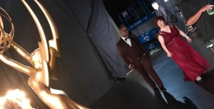 An African American man and a white woman dressed in a tux and gown back stage