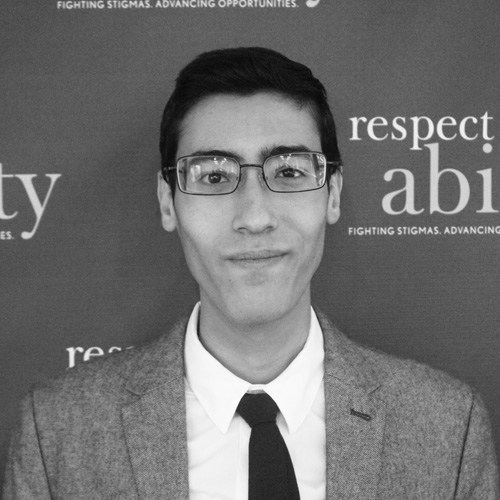 Respectability Fellow Adam Srayi standing in front of the RespectAbility logo smiling