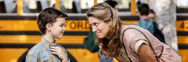 Nine-year-old Sheldon wearing a bow tie talking to his mom in front of a school bus