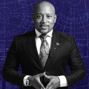 Daymond John in a black and white photo of him wearing a suit against a blue background