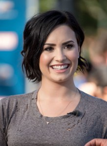 Demi Lovato smiling wearing a brown top