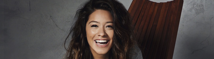 Gina Rodriguez smiling, seated on a chair