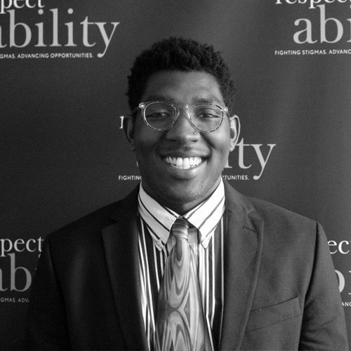 Respectability Fellow Christopher Coleman smiling in front of the Respectability banner