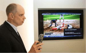 Tom Wlodkowski holding a remote in front of a wall mounted TV showing a baseball game