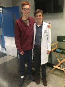 Coby Bird and Freddie Highmore standing and posing on set for the camera