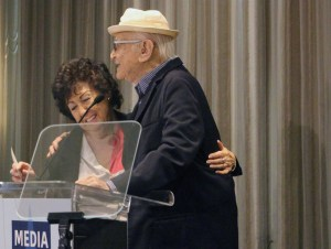 Fern Field and Norman Lear hugging behind the poidum