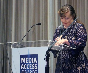 Jamie Brewer tanding at a podium with the sign Media Access Awards