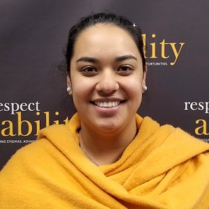 RespectAbility fellow Juliet Arcila Rojas smiling in front of the RespectAbility banner