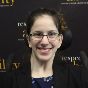 RespectAbility fellow Sarah Bram smiling in front of the RespectAbility banner