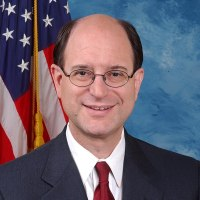 Rep. Brad Sherman smiling in front of an American flag
