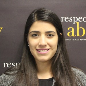 RespectAbility Fellow Ana Lucia Figueroa smiling in front of the RespectAbility banner