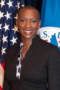 Claudia Gordon standing in front of two flags, smiling.