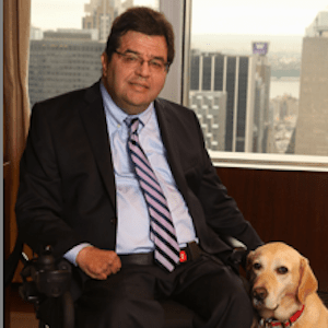 Jim Sinocchi sitting in front of a window with his dog by his side