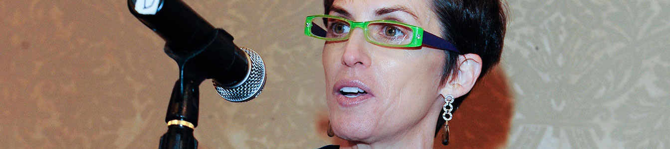 close up of Deborah Calla's face wearing green glasses behind a microphone