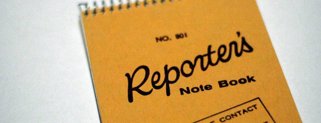 "A notebook that says ""Reporter Note Book"" on the cover"