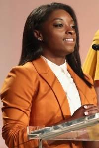 Simone Biles speaking at a podium wearing an orange blazer and white shirt