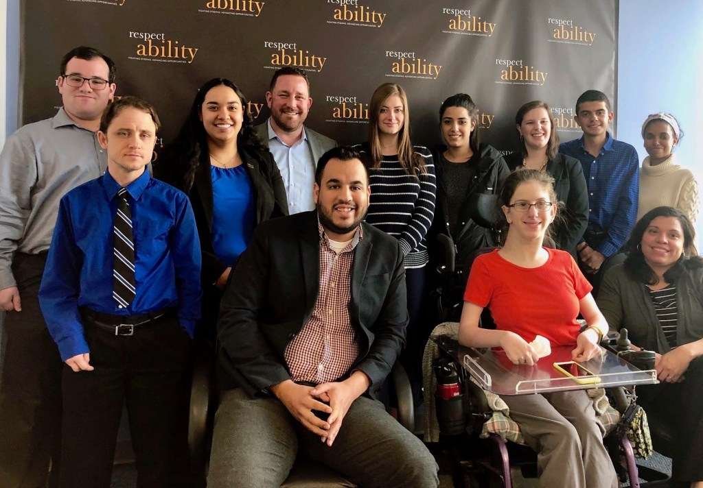 Aaron Dorfman with RespectAbility staff and Fellows in front of the RespectAbility banner