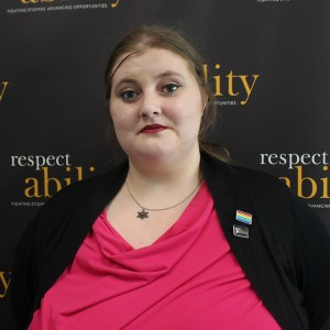 Headshot of Lily in professional dress in front of RespectAbility banner