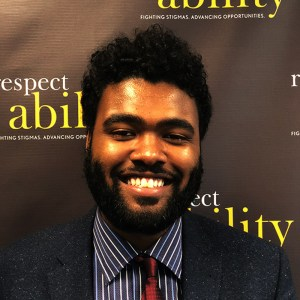 Zavier Taylor in professional dress in front of respectability sign