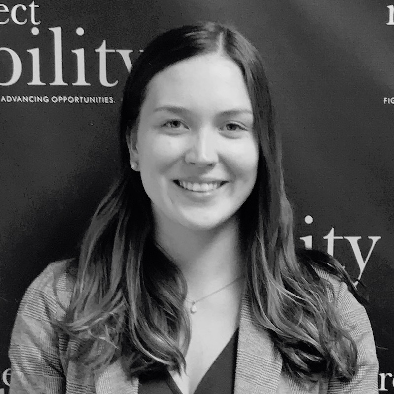 Laura Haney smiling in front of the RespectAbility banner