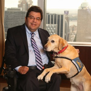 Jim Sinocchi sitting with a service dog in front of a window with skyscrapers behind him.