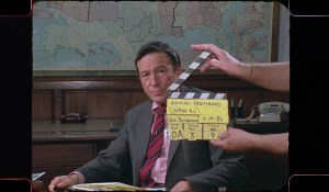 Mike Wallace about to start filming a 60 minutes piece, sitting in front of a world map with the director holding the clapperboard