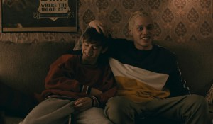 Griffin Gluck and Pete Davidson sitting on a couch. Pete has his hand on Griffin's head