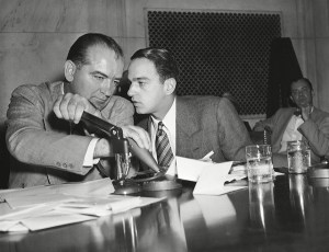 Roy Cohn and another man having a conversation at a desk with lots of papers and a hole puncher on it.