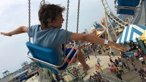 A young girl on a giant swing ride at an amusement park