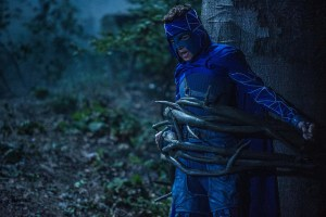 Mihajlo Milavic in a blue superhero outfit tied to a tree in the woods